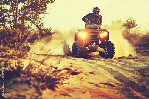 Fototapety, obrazy: Teen riding ATV in sand dunes making a turn in the sand
