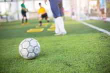Soccer Ball On Green Artificial Turf With Blurry Of Yellow Ring Marker And Player Training.