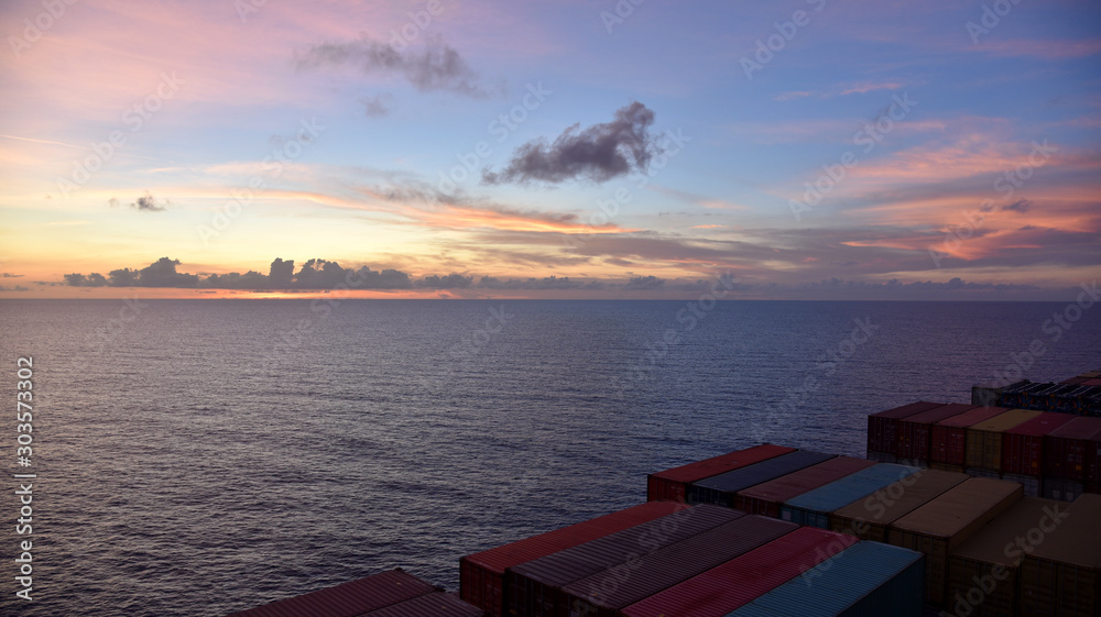 Cargo ship sailing through the ocean during a beautiful sunset, view on the cargo deck with containers from the navigation bridge.