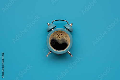 Obraz Alarm clock as coffee cup on blue background. Top view. Flat lay. Good morning concept - fototapety do salonu