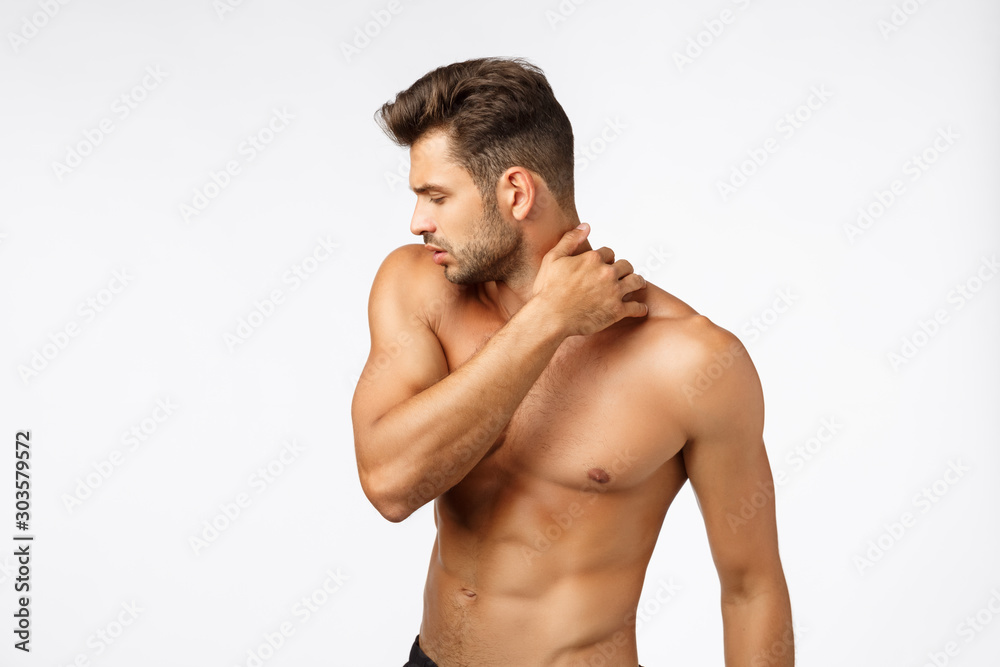 Fototapeta Beauty, wellbeing, workout and sports concept. Handsome sexy tanned caucasian guy with naked torso, turn away, touching neck, bodybuilder showing perfect body, standing white background
