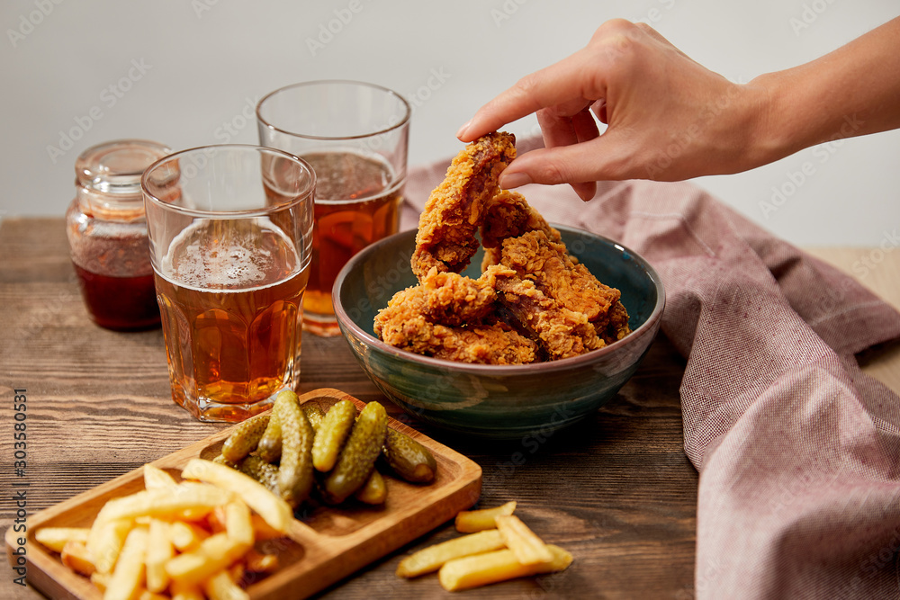 Fototapeta cropped view of woman eating delicious chicken nuggets, french fries and gherkins near glasses of beer on wooden table isolated on grey