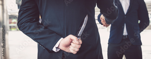 Fotomural two business making handshake a deal but hiding knives