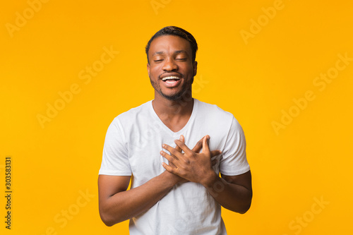 Photo Touched Black Man Pressing Hands To Chest Standing, Yellow Background