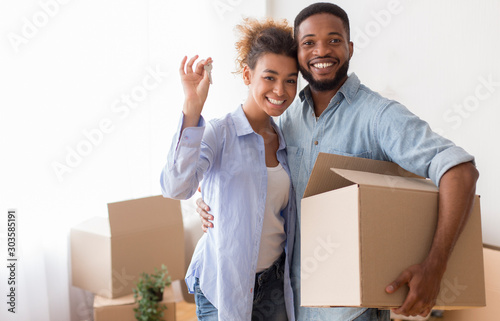 Fotografie, Obraz Couple Showing Key Holding Moving Box Standing In New Home