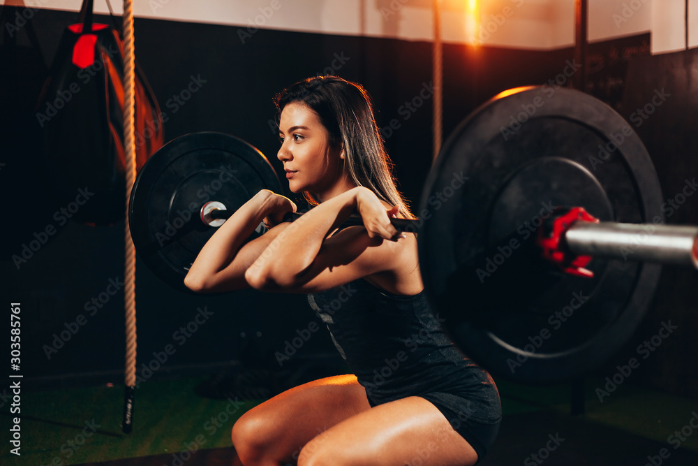 Fototapeta Muscular woman in gym doing heavy weight exercises. Young woman doing weight lifting at health club