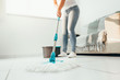 canvas print picture - Cropped image of young woman in using a mop while cleaning floor in the house
