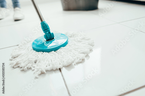 Obraz na płótnie Cropped image of young woman in using a mop while cleaning floor in the house