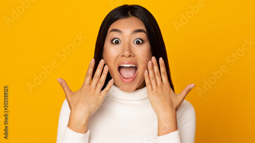 Wow. Surprised asian girl shouting over yellow background Canvas Print