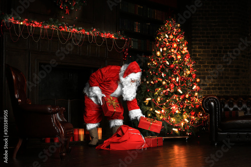 Canvas Prints Coffee bar Christmas night, Santa Claus puts gifts under the tree