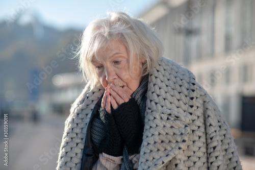 Valokuva Grey-haired homeless pensioner feeling very cold outside