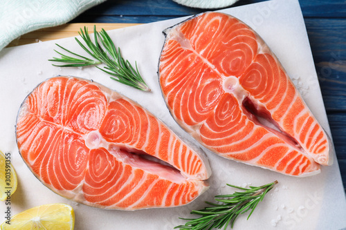 Fresh raw salmon with lemon and rosemary on parchment, flat lay. Fish delicacy
