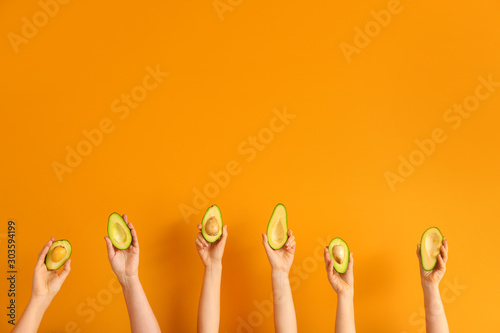 Obraz Female hands with fresh avocados on color background - fototapety do salonu