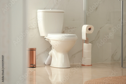 Fotomural  Modern toilet bowl with roll of paper in bathroom