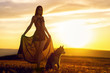 canvas print picture - Beautiful young girl in a light flying dress at sunset in the mountains with a husky dog. A warm sunset light illuminates and falls on a girl and her dog
