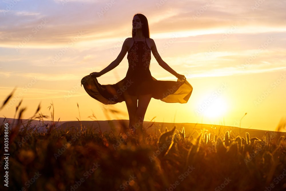 Fototapety, obrazy: Silhouette of a beautiful girl in a light dress at sunset in the mountains.