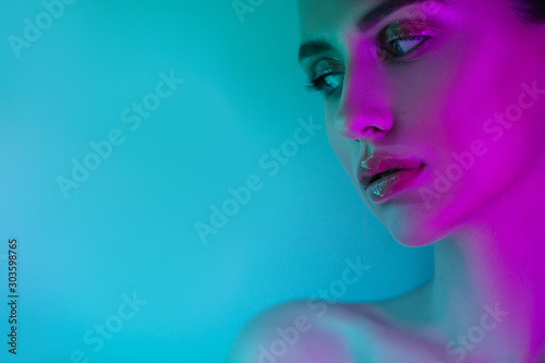 High Fashion woman in colorful bright neon uv blue and purple lights, posing in studio, beautiful girl, glowing make-up, colorful make up Fototapet