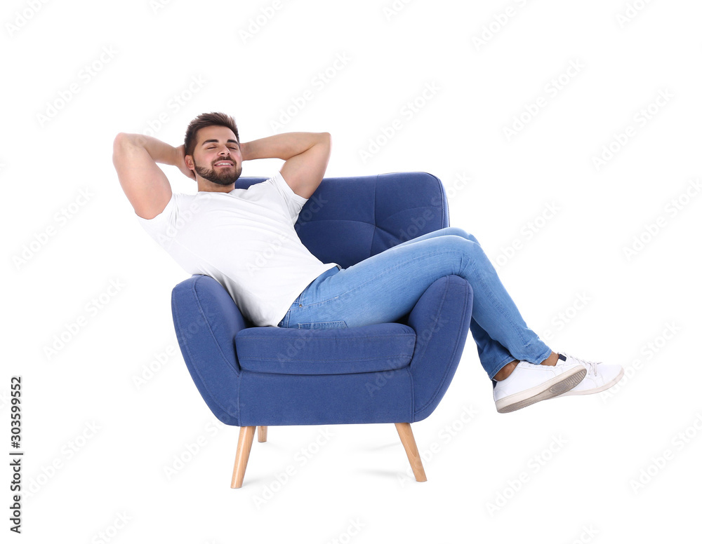 Fototapeta Young man resting in armchair isolated on white