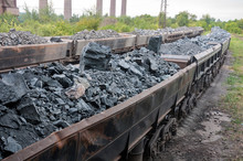 Train Of Tipping Cars Loaded With Raw Iron Ore At Wagon Unloading Platform Of Ore Dressing Factory On Industrial Background