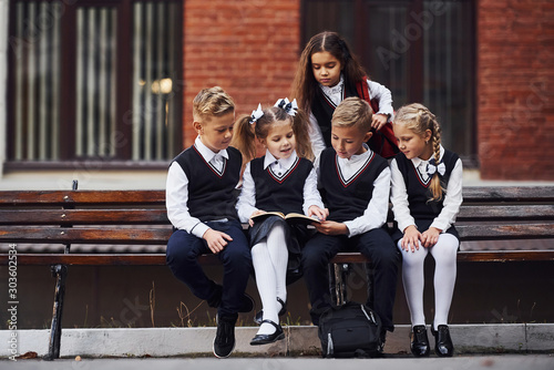 Fotografie, Obraz School kids in uniform that sits outdoors on the bench with notepad