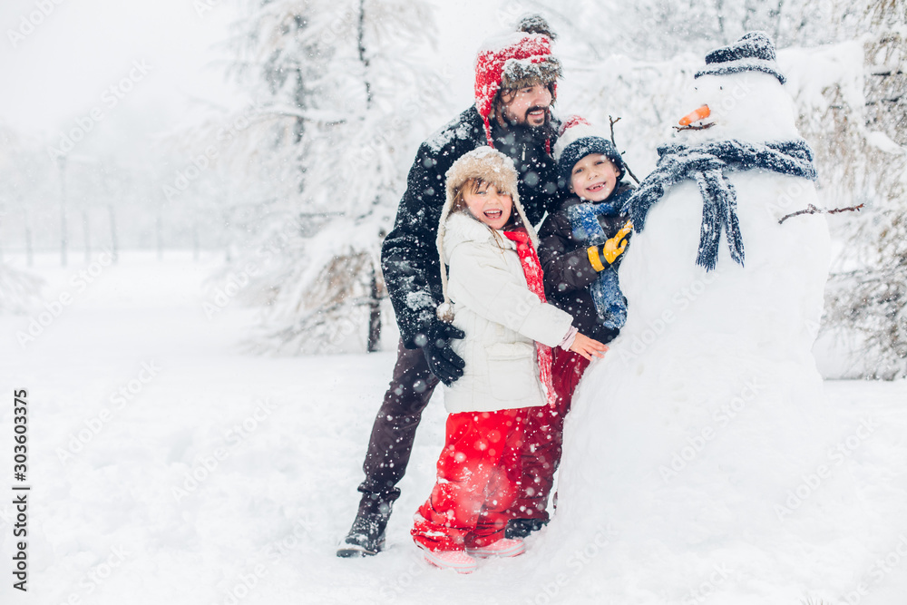 Fototapeta Dad with children playing in snow