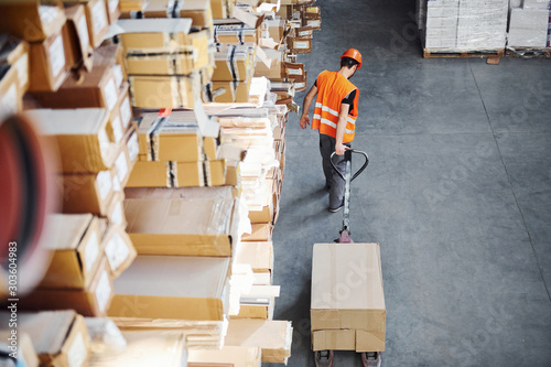 Obraz Young male worker in uniform is in the warehouse pushing pallet truck - fototapety do salonu