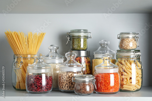 Photographie Glass jars with different types of groats and pasta on white shelf