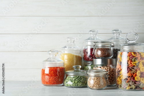 Fototapeta Glass jars with different types of groats and pasta on white wooden table obraz