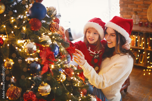 Obraz Smiling mom and daughter decorating Christmas tree - fototapety do salonu