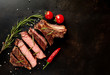 Beef steak, herbs and spices on a stone background, top view