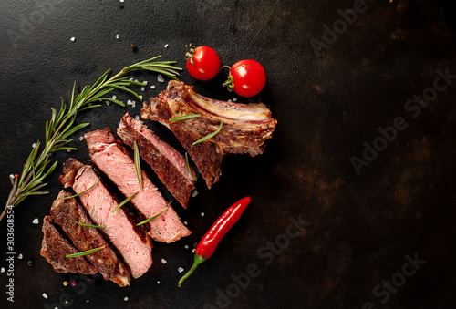 Obraz Beef steak, herbs and spices on a stone background, top view - fototapety do salonu