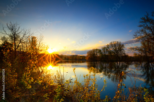Long exposure sunset or sunrise over river side of Mississippi and the sun is reflex with water surface and distribution sun rays and small trees in foreground and clear blue sky