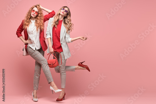 Fashionable woman with stylish hairstyle, makeup dance. Two Shapely blonde redhead girl having fun, trendy red outfit, heels, fashion hair, make up. Excited model, beauty dancing fun concept on pink - fototapety na wymiar