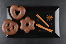 Traditional German Christmas Chocolate Gingerbread Lebkuchen With Cinnamon Sticks, Anise And Clove On Black Plate