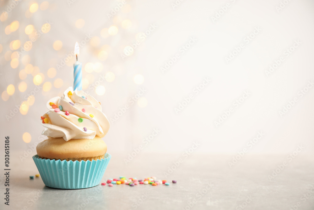 Fototapety, obrazy: Birthday cupcake with candle on light grey table against blurred lights. Space for text