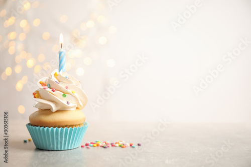 Birthday cupcake with candle on light grey table against blurred lights фототапет
