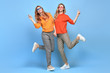 Two Lovable fashionable woman sisters dance in Trendy sunglasses, orange outfit. Studio shot of Carefree beautiful funny stylish friends smiling on blue. Happy fashion girl, dancing fun positive mood