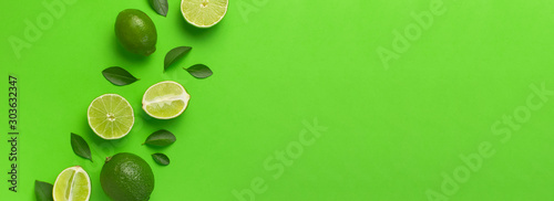 Fresh juicy lime and green leaves on bright green background. Top view flat lay copy space. Creative food background, tropical fruit, vitamin C, citrus. Composition with whole and slices of lime - 303632347
