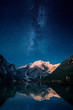 canvas print picture - Beautiful first light on a mountain top against stars and milky way in Lago Di Praies, Dolomites, Italy. Two image composite.