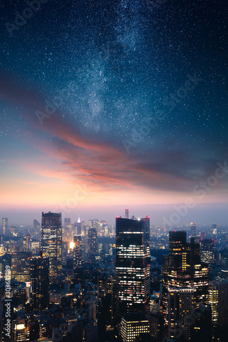 Fototapeta Dramatic cityscape with epic clouds and the stars of the milky way obraz