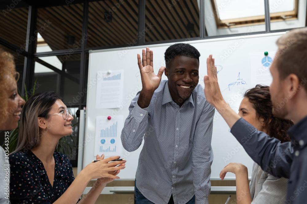 Fototapeta Happy african american team leader giving high five to partner.