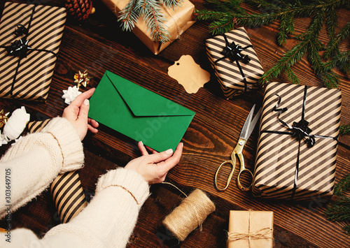Woman holding envelope near gifts on a table