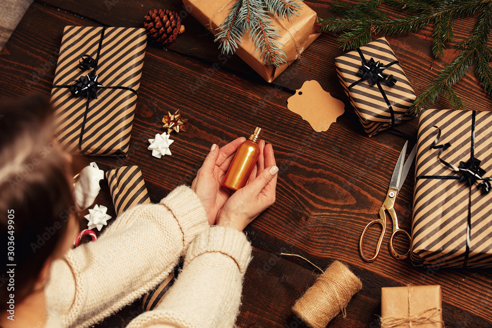 Fototapeta Woman wrapping a perfume bottle as a Christmas gift