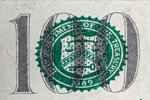 A Number Of One Hundred On Dollar Bill And United States Treasury Department Symbol In Macro Magnification