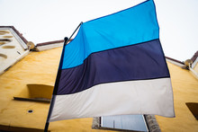 Estonia Flag In Front Of Old Building Of Tallinn Old Town.