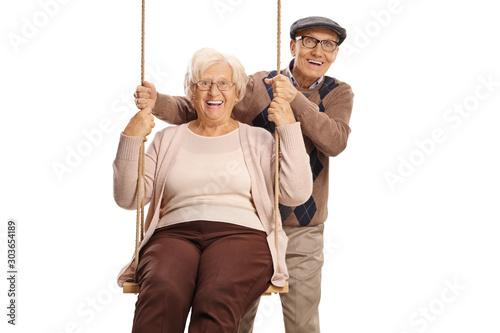 Fototapety, obrazy: Elderly man pushing an elderly woman on a swing