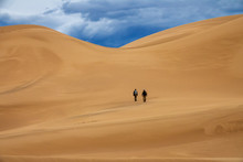 Two Travelers In The Desert. Hiking On Sand Dunes In Mountains. Gobi Desert, Mongolia
