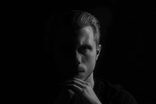 Black And White Portrait Of Young Serious Looking Man. Low Key, Dark Background Studio Shot.