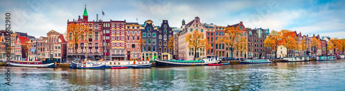 Obraz Panoramic autumn view of Amsterdam city. Famous Dutch channels and great cityscape. Colorful morning scene of Netherlands, Europe. Traveling concept background. - fototapety do salonu