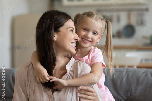 Preschool girl cuddling from back smiling young mother. Canvas Print
